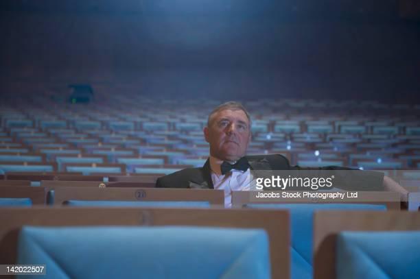 Caucasian man in tuxedo sitting in dark, empty auditorium watching movie