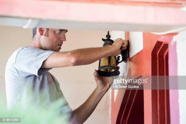 Caucasian man installing light above door