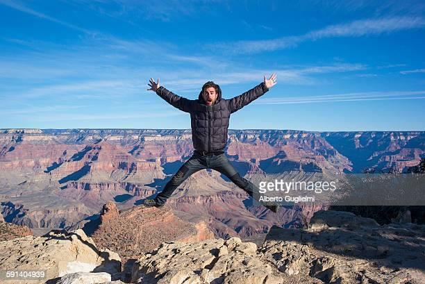 Caucasian man jumping at Grand Canyon, Arizona, United States