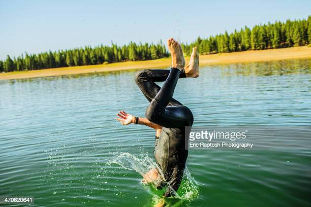 Caucasian man jumping into rural lake