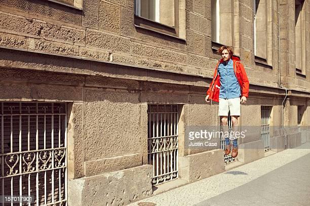 A caucasian man jumping through the city