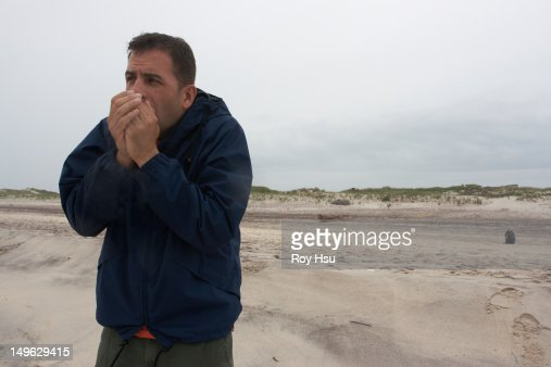 Caucasian man keeping warm on beach : Stock Photo