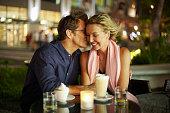 Caucasian man kissing wife in restaurant