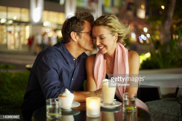 Caucasian man kissing wife in restaurant