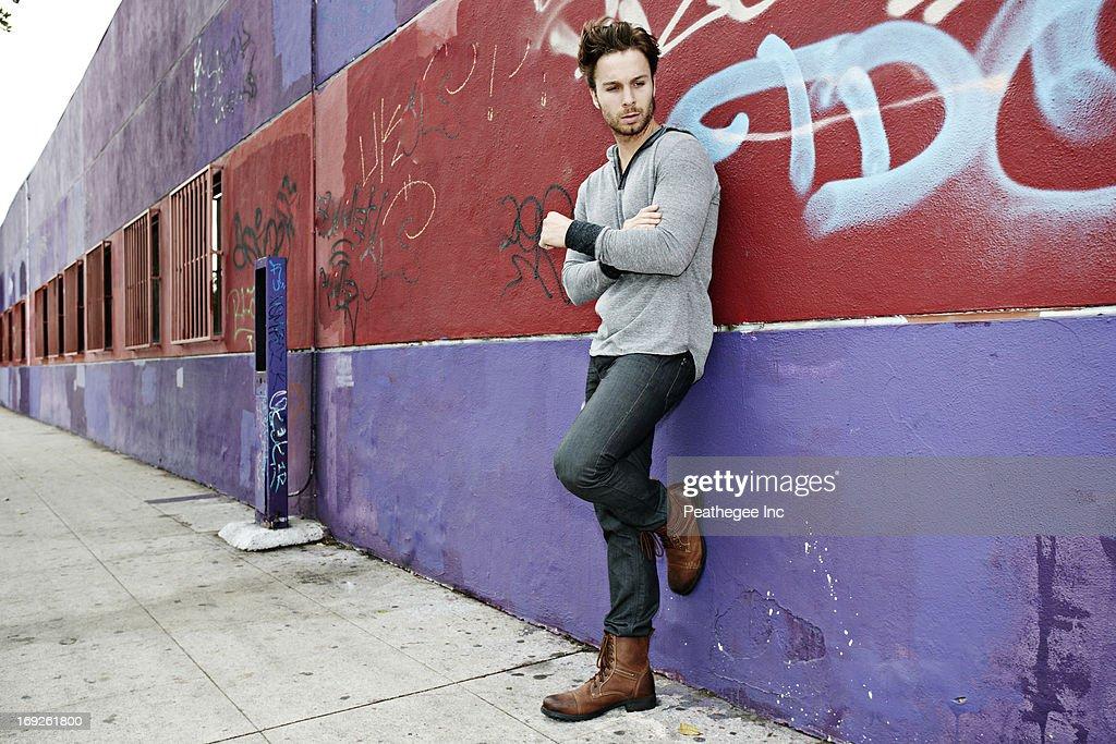 Caucasian man leaning against graffiti wall : Stock Photo