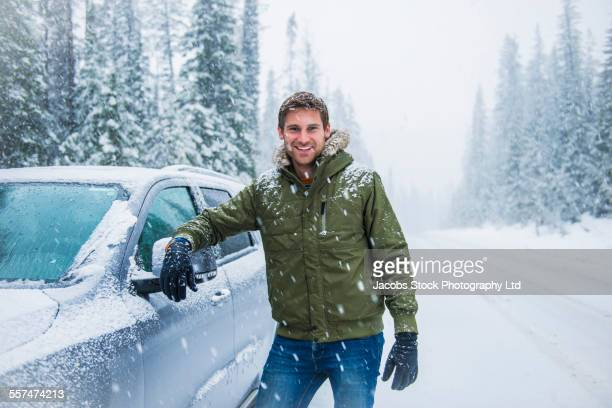 Caucasian man leaning on car in snow