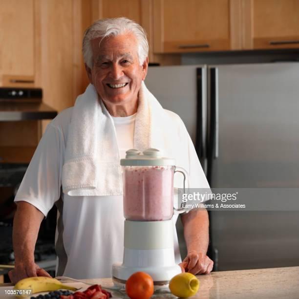 Caucasian man making smoothie in kitchen