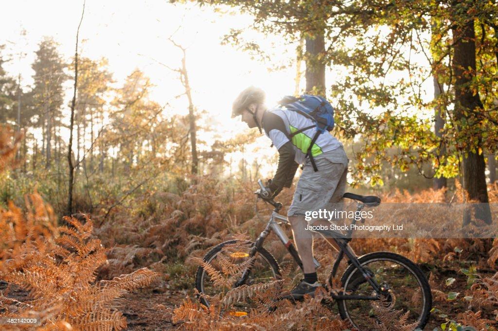 Caucasian man mountain biking on trail