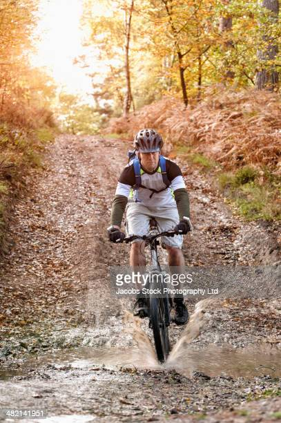 Caucasian man mountain biking through muddy puddle