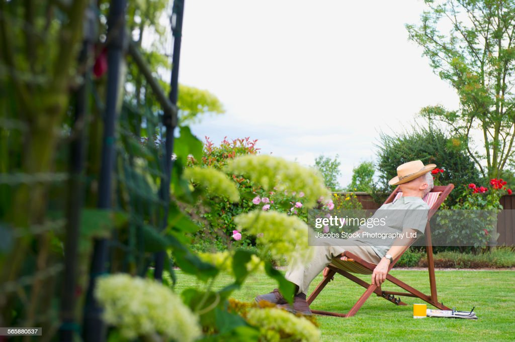 Caucasian man napping in lawn chair in backyard