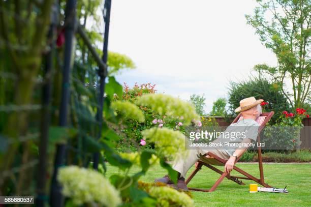 Caucasian man napping in lawn chair in backyard