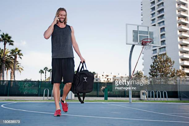 Caucasian man on basketball court talking on cell phone