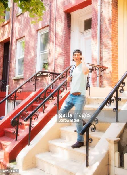 Caucasian man on front stoop of urban brownstone