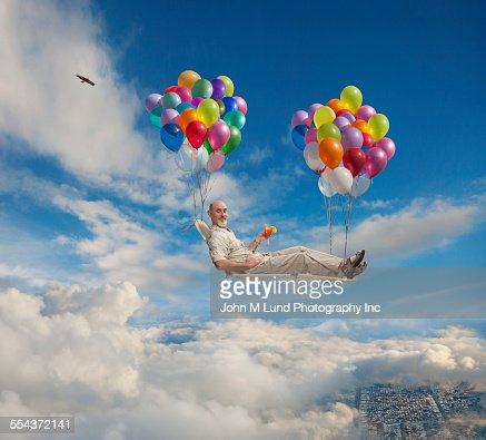 Caucasian man on lawn chair floating with balloons in sky