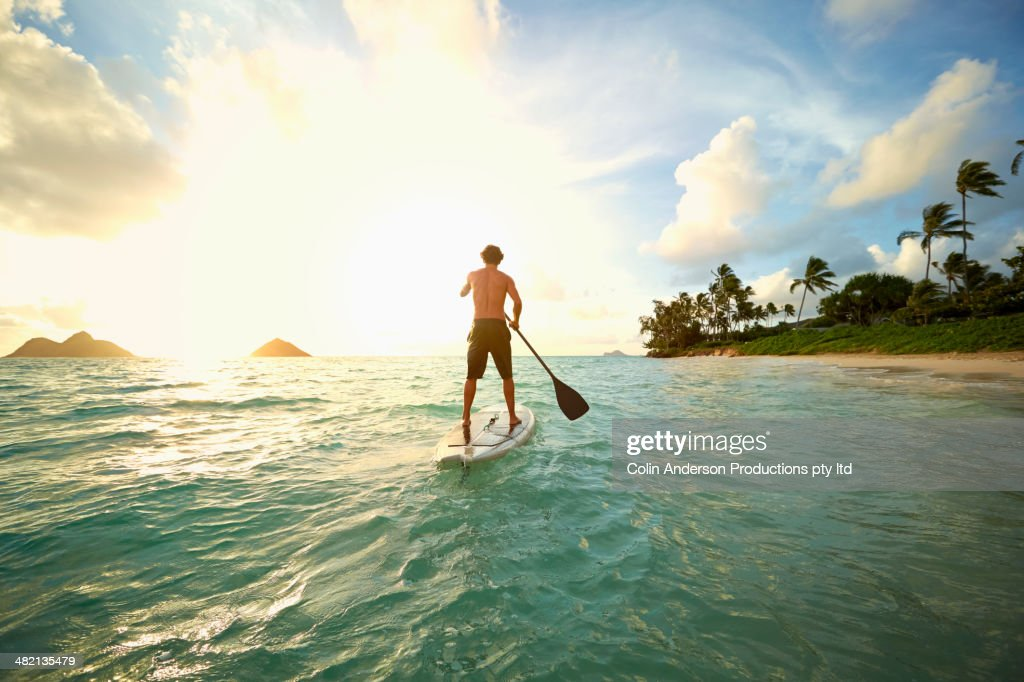 Caucasian man on paddle board in ocean : Stock Photo