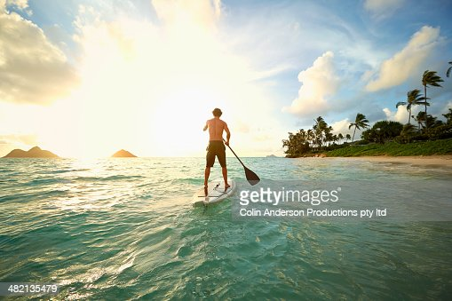 Caucasian man on paddle board in ocean : Stock-Foto