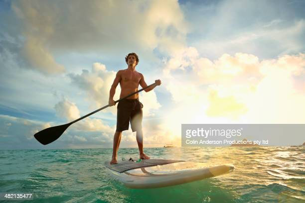 Caucasian man on paddle board in water