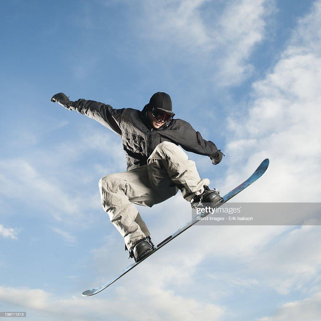 Caucasian man on snowboard in mid-air