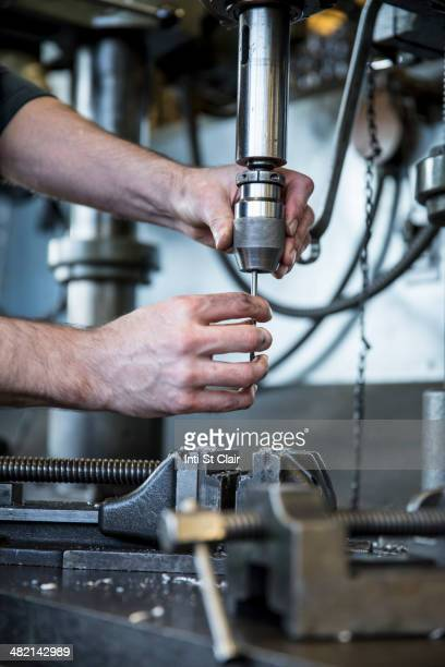 Caucasian man operating drill machinery in metal shop
