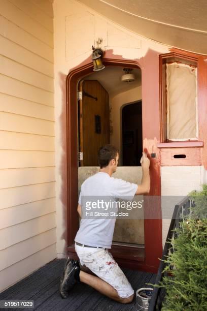 Caucasian man painting door frame
