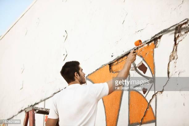 Caucasian man painting wall
