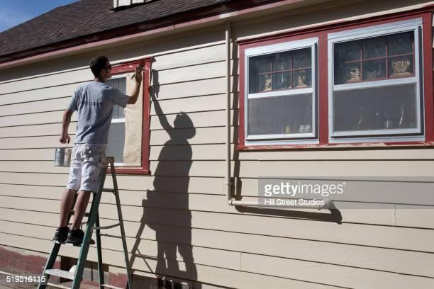 Caucasian man painting window frames