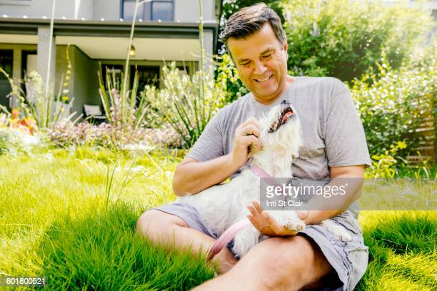 Caucasian man petting dog in grass