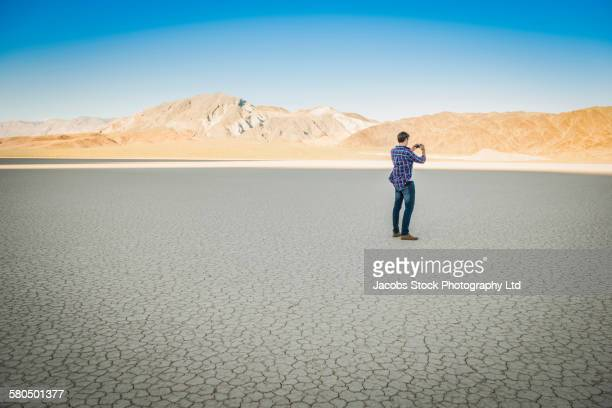 Caucasian man photographing cracked desert landscape