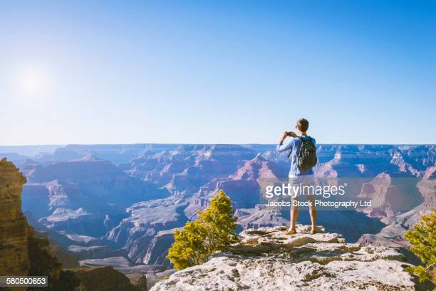 Caucasian man photographing desert landscape, Grand Canyon, Arizona, United States
