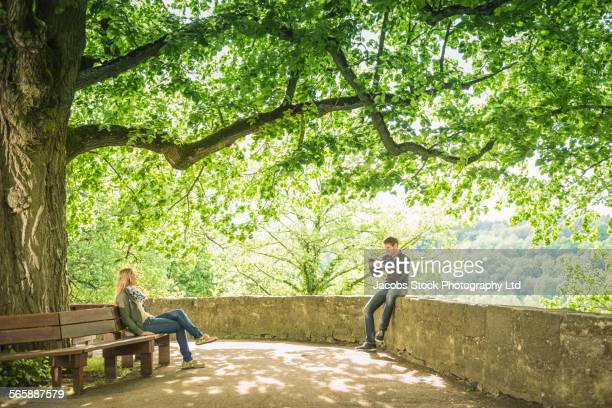 Caucasian man photographing girlfriend on park bench