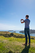 Caucasian man photographing scenic view of ocean and landscape