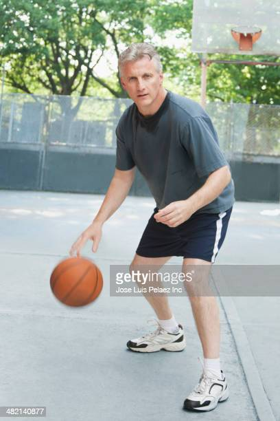 Caucasian man playing basketball on court