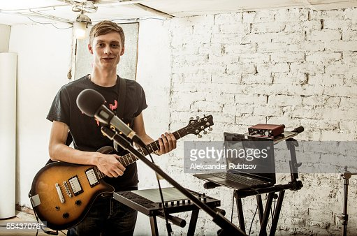 Caucasian man playing electric guitar in rock band