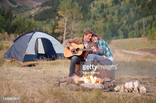Caucasian man playing guitar for wife near campfire : Stock Photo