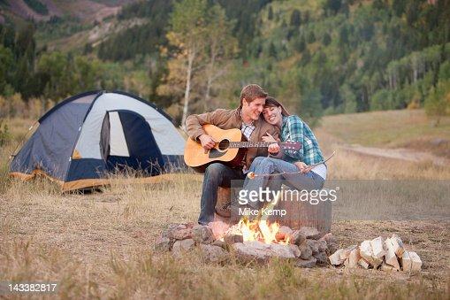 Caucasian man playing guitar for wife near campfire : Foto stock