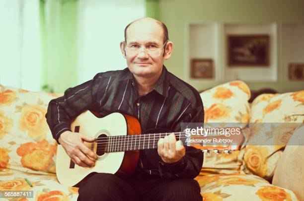 Caucasian man playing guitar on sofa