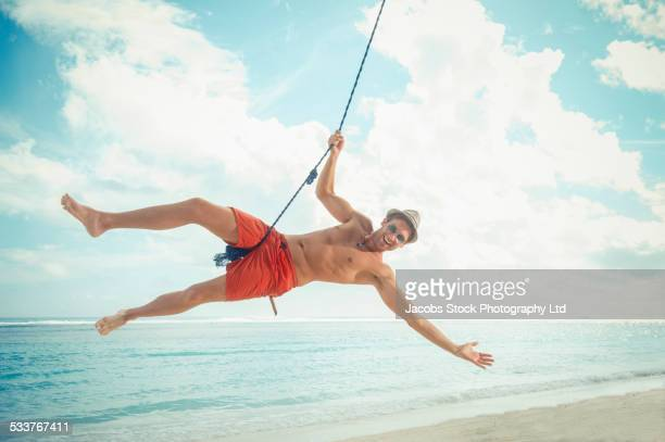 Caucasian man playing on rope swing on tropical beach