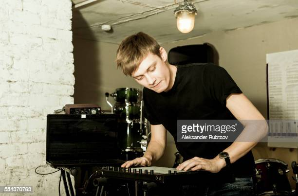Caucasian man playing synthesizer in rock band