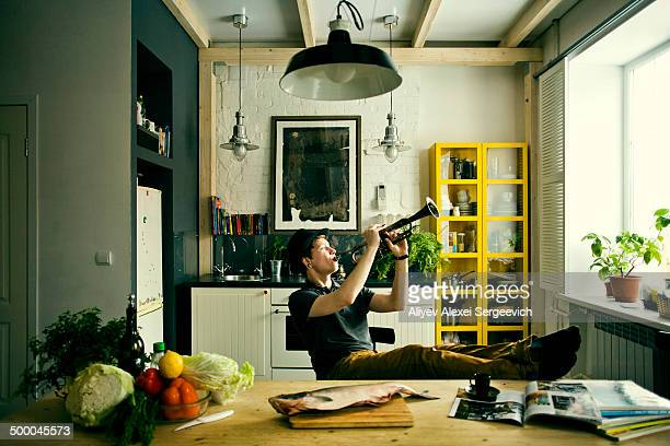 Caucasian man playing trumpet in kitchen