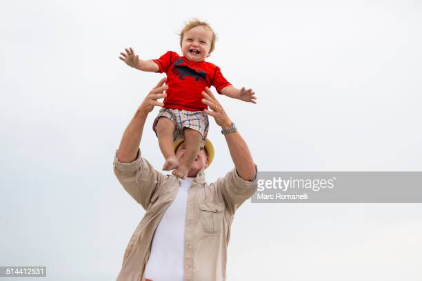 Caucasian man playing with grandson outdoors