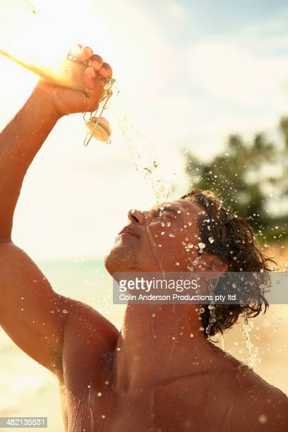 Caucasian man pouring water over face on beach