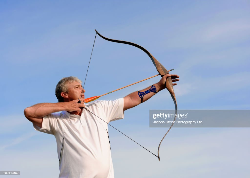 Caucasian man practicing archery outdoors