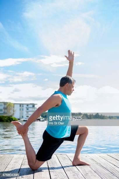 Caucasian man practicing yoga on wooden dock