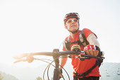 Caucasian man pushing mountain bike