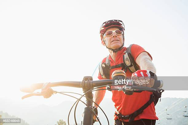 Caucasian man pushing mountain bike