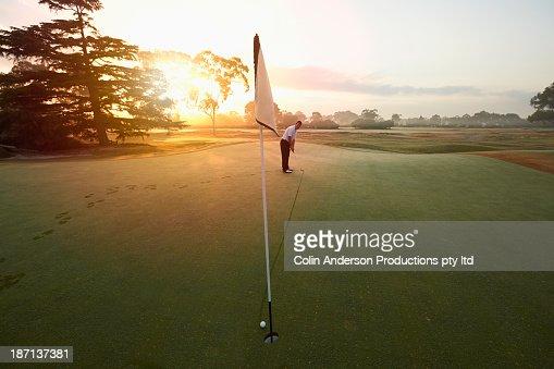 Caucasian man putting on golf course