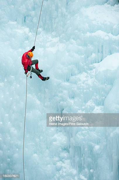 Caucasian man rappelling down ice wall