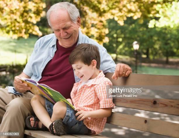 Caucasian man reading book to grandson in park