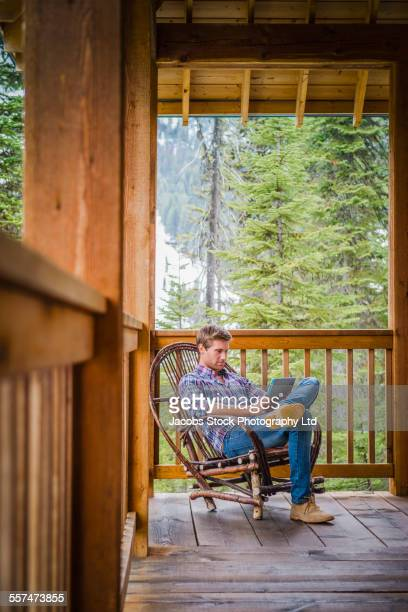 Caucasian man reading in rocking chair on log cabin porch