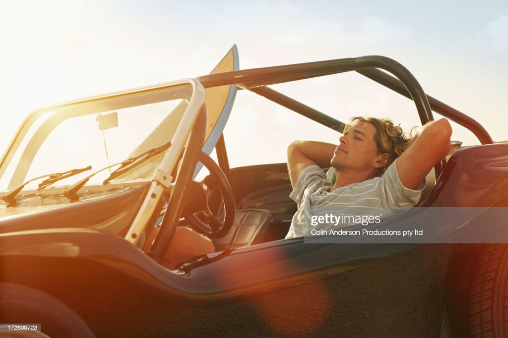 Caucasian man relaxing in jeep : Stock Photo